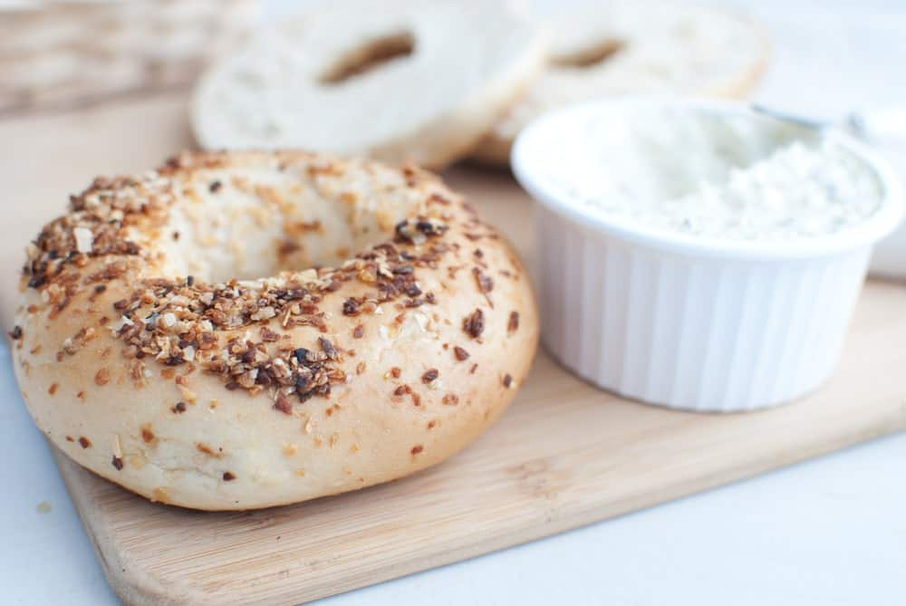 A piece of garlic bagel with a side of cream cheese.