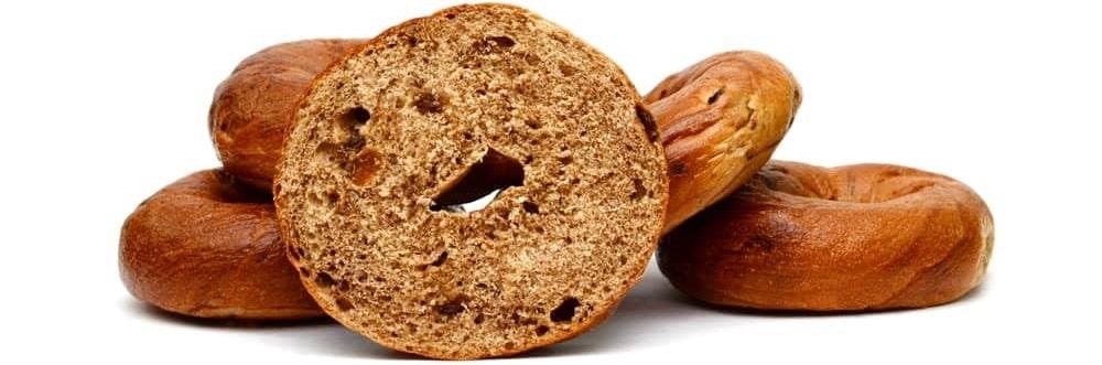 A half cut bagel with cinnamon and raisins.