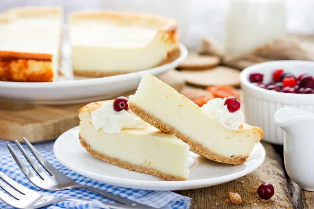 Two slices of Classic Cheesecake on a plate.