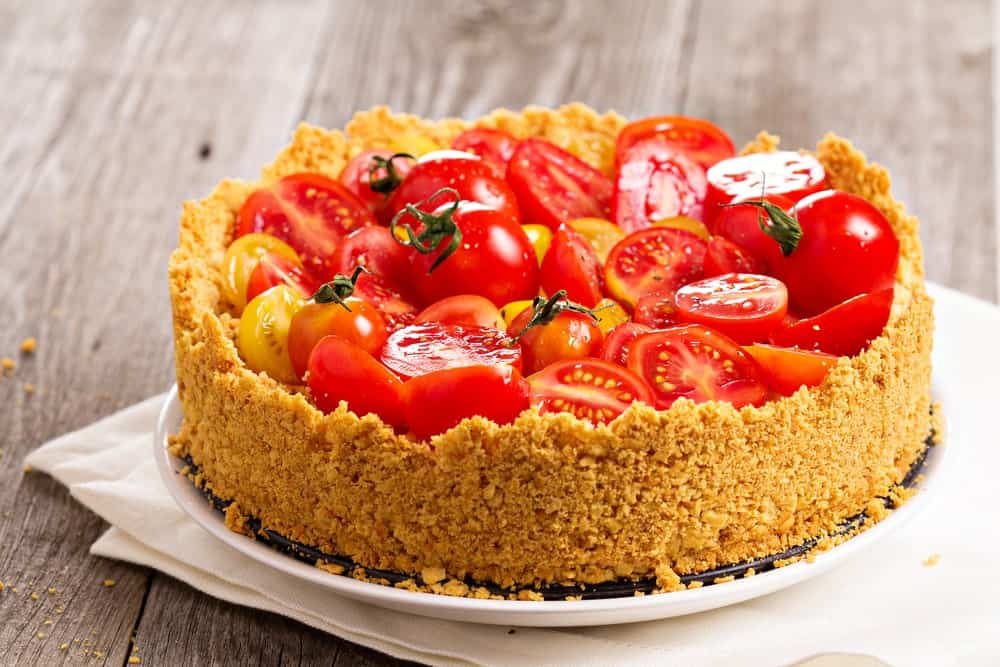 A whole Savory Cheesecake with tomatoes on top.