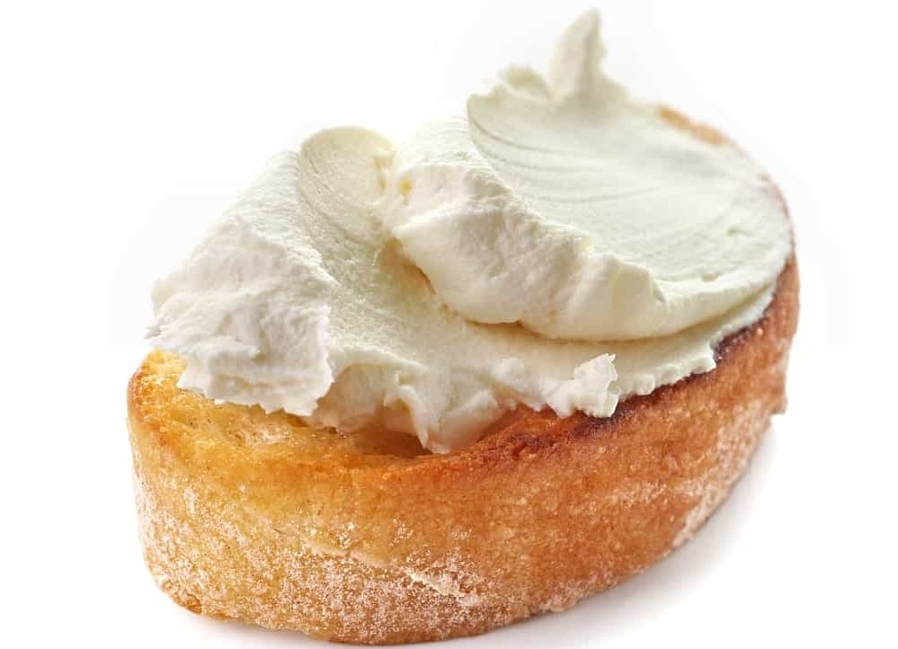 A piece of pastry topped with cream cheese.