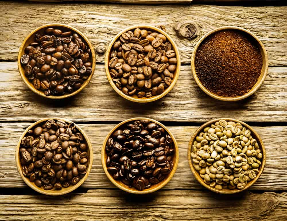 Various types of coffee beans in bowls on top of a rustic table.