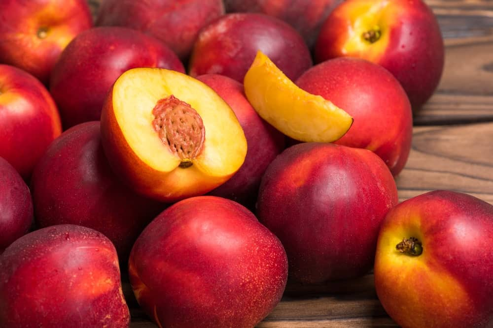 Nectarines on top of a wood plank table.