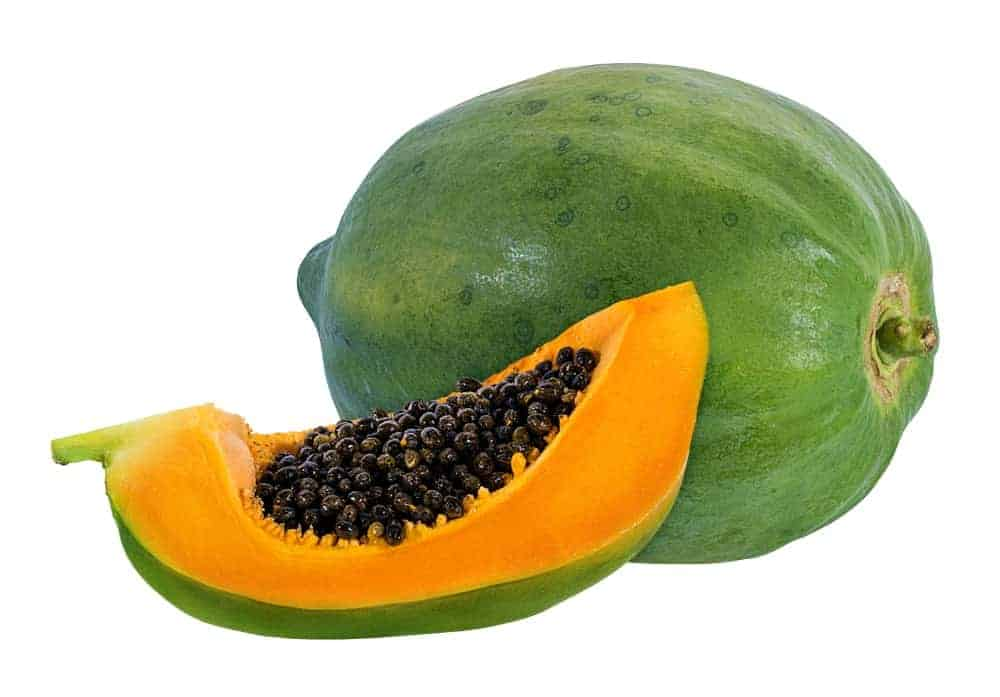 A whole papaya with a slice on the side.