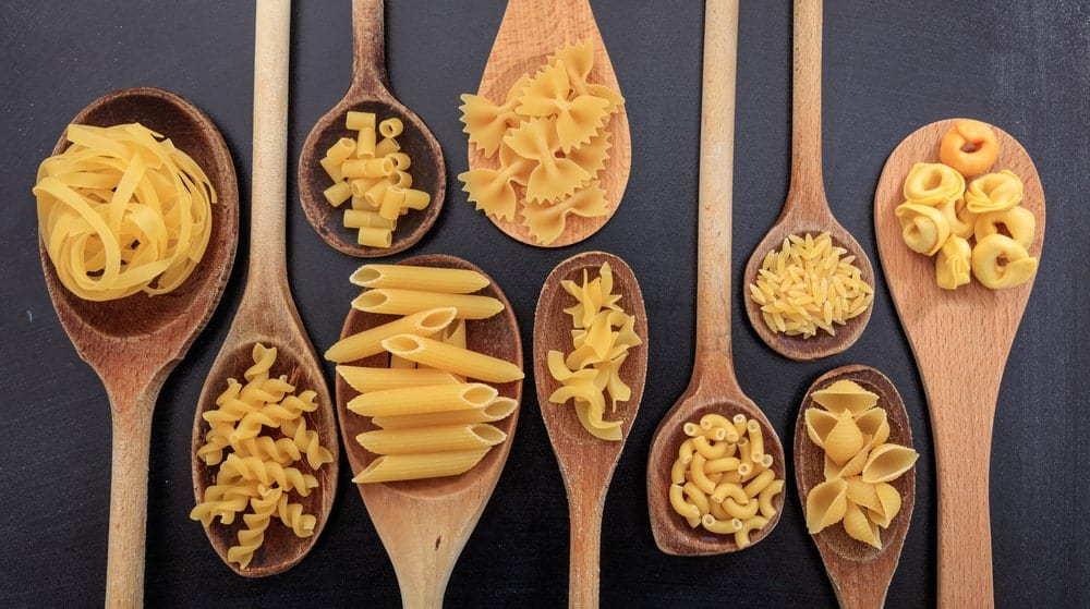 Various types of pasta placed on wooden spoons.