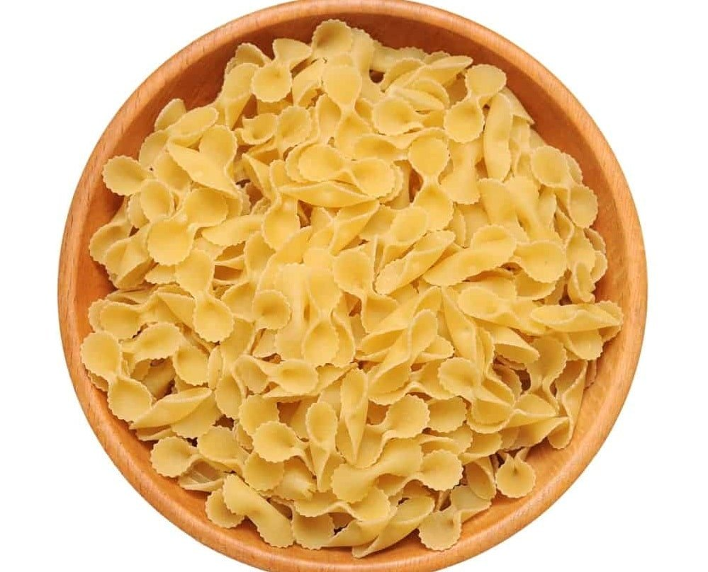 A wooden bowl filled with Farfalle rotonde pasta.