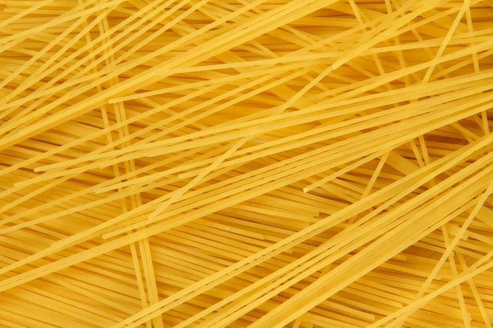 A close look at uncooked spaghettini pasta.