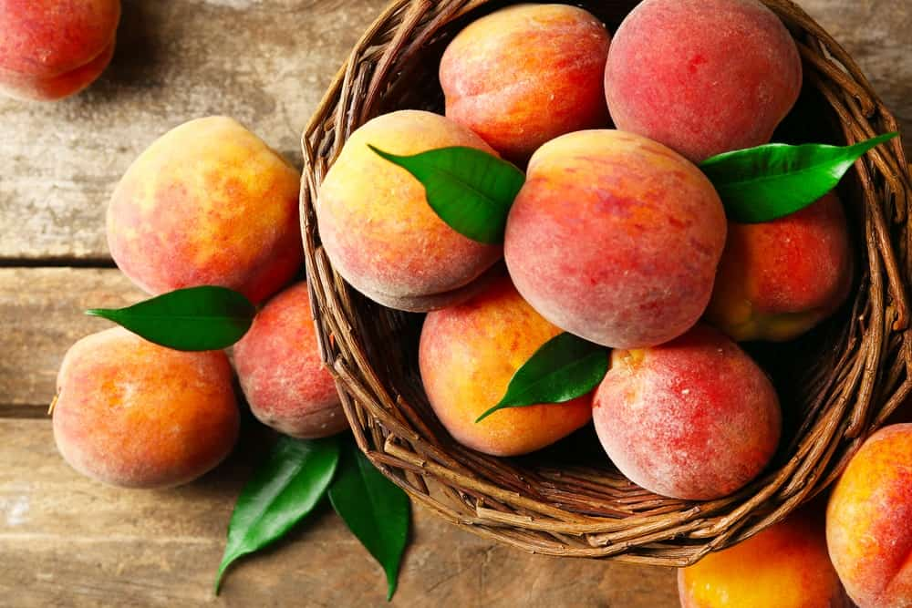 A basketful of peaches over a wood plank table.