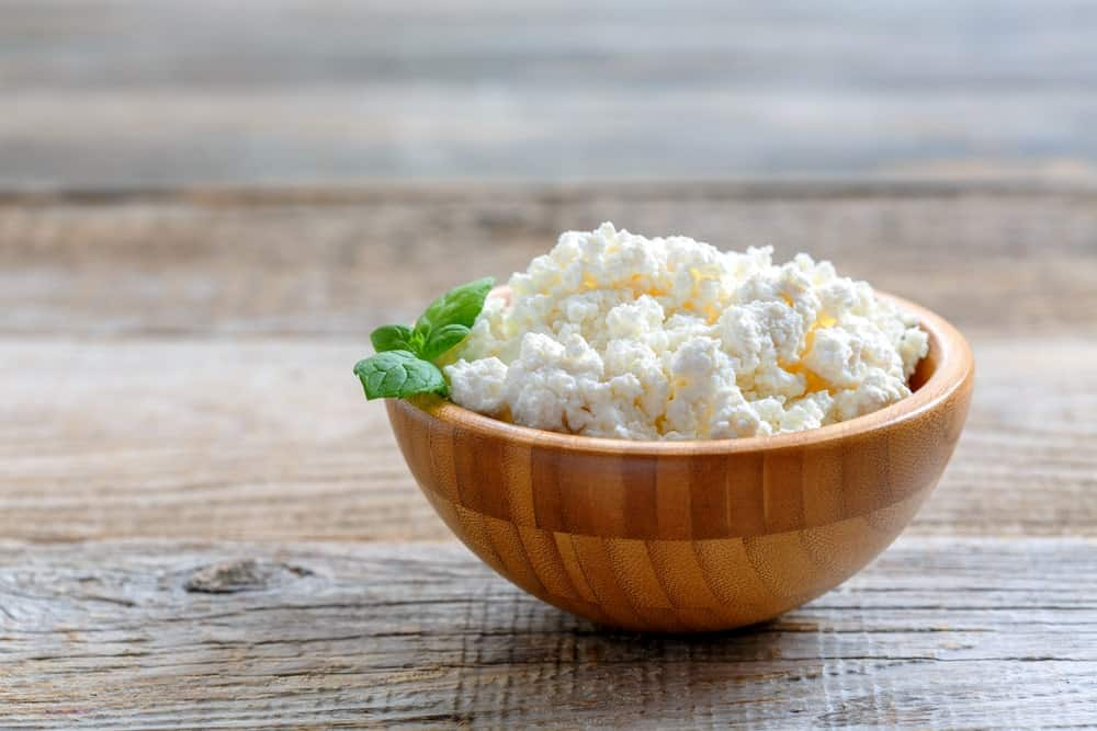 A wooden bowl of homemade Cottage Cheese.