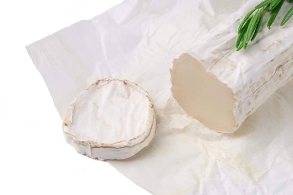 A slice roll of goat cheese on a paper sheet.