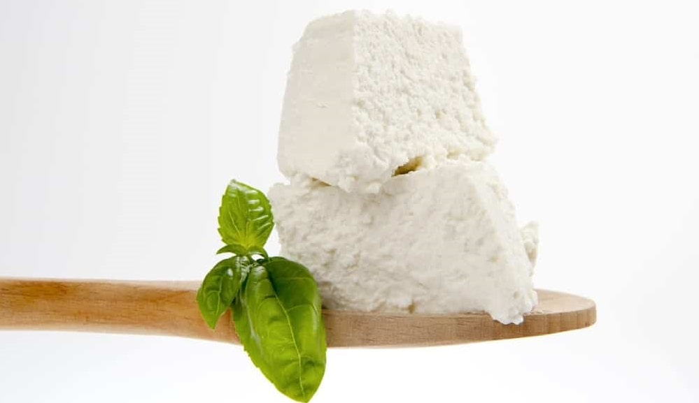 Fresh Ricotta Cheese on a wooden spoon.