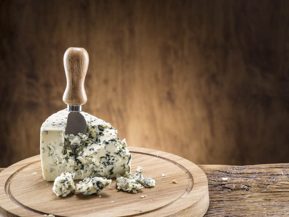 A wedge of blue cheese on a chopping board.