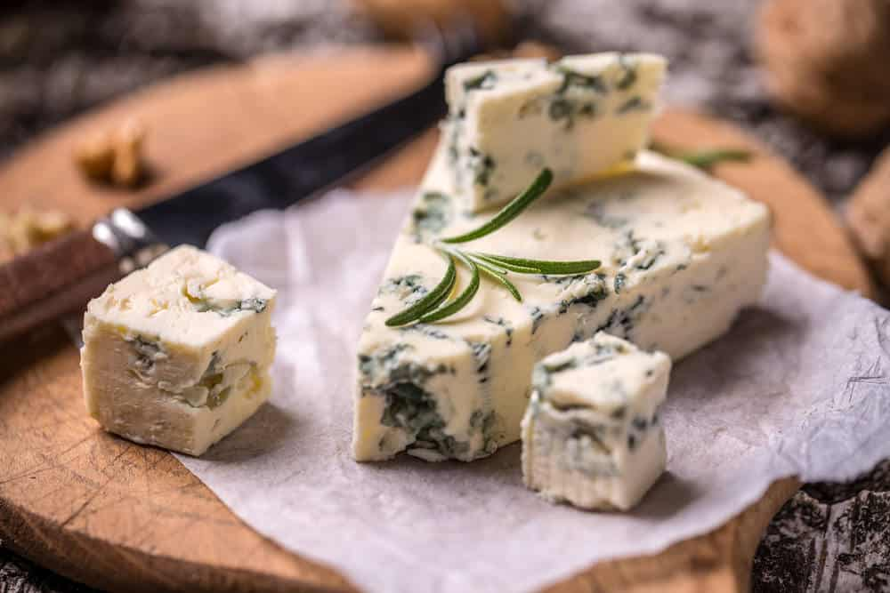 A slice of roquefort cheese on a chopping board.