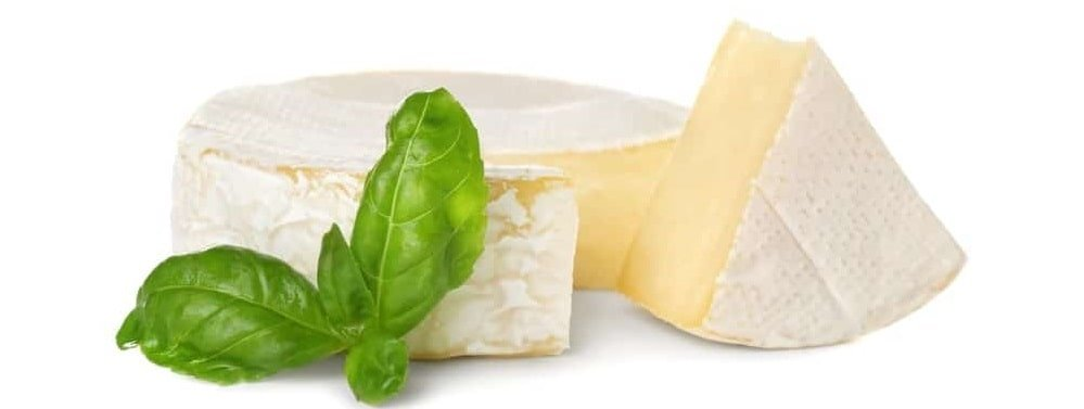 A sliced wheel of brie cheese with fresh basil on the side.