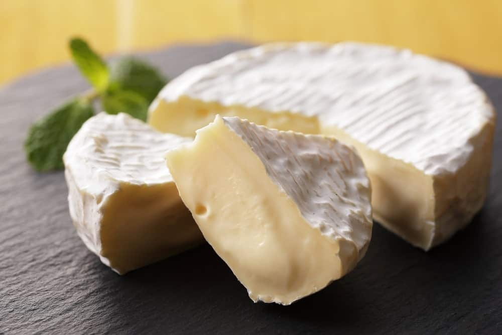 A sliced wheel of Camembert Cheese.