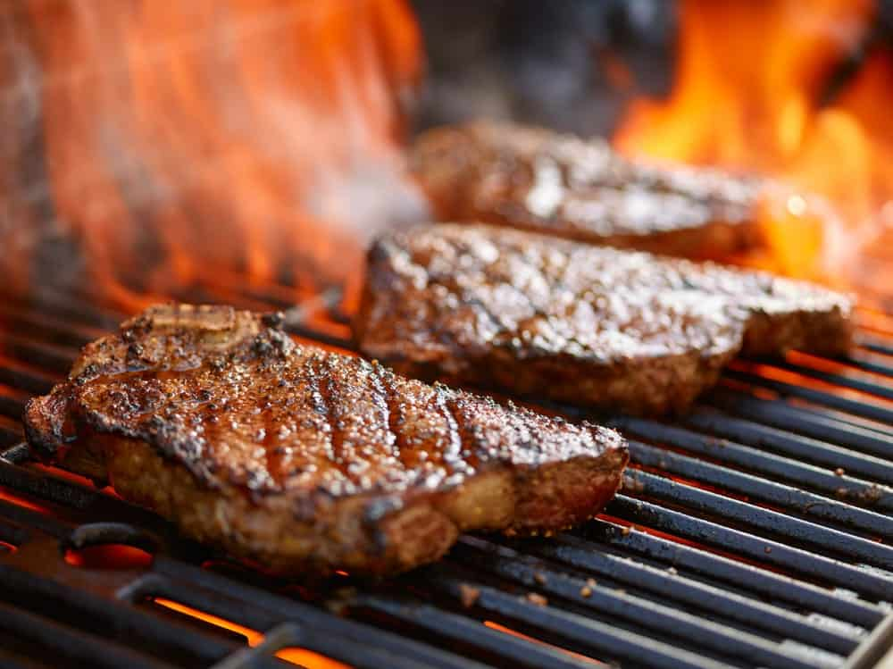 Three pieces of steak being flame-grilled.