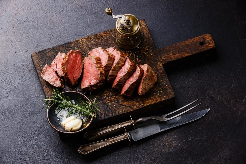 Sliced beef tenderloin with garlic and herbs on the side.