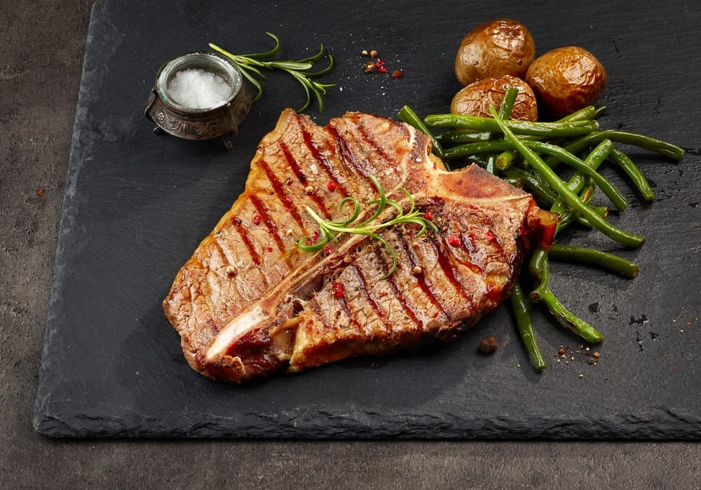 A piece of grilled T-bone steak with roasted vegetables on the side.