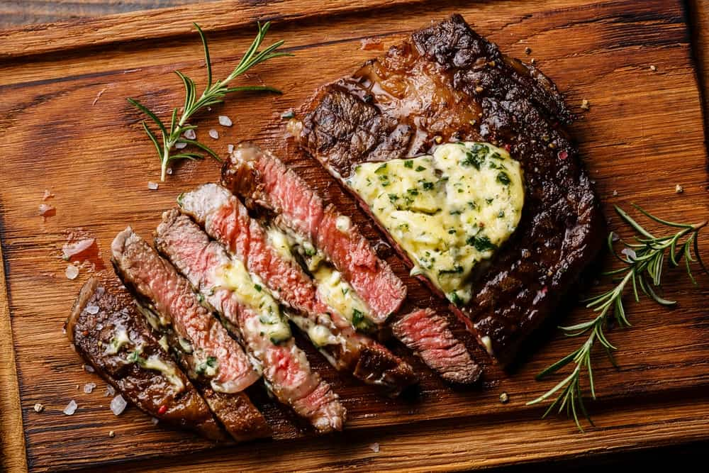 A piece of ribeye steak with herb butter and rosemary.