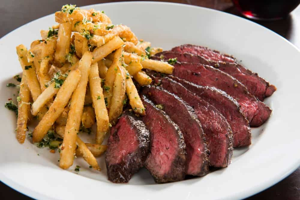 Pieces of sliced hanger steak on a plate with herb fries.