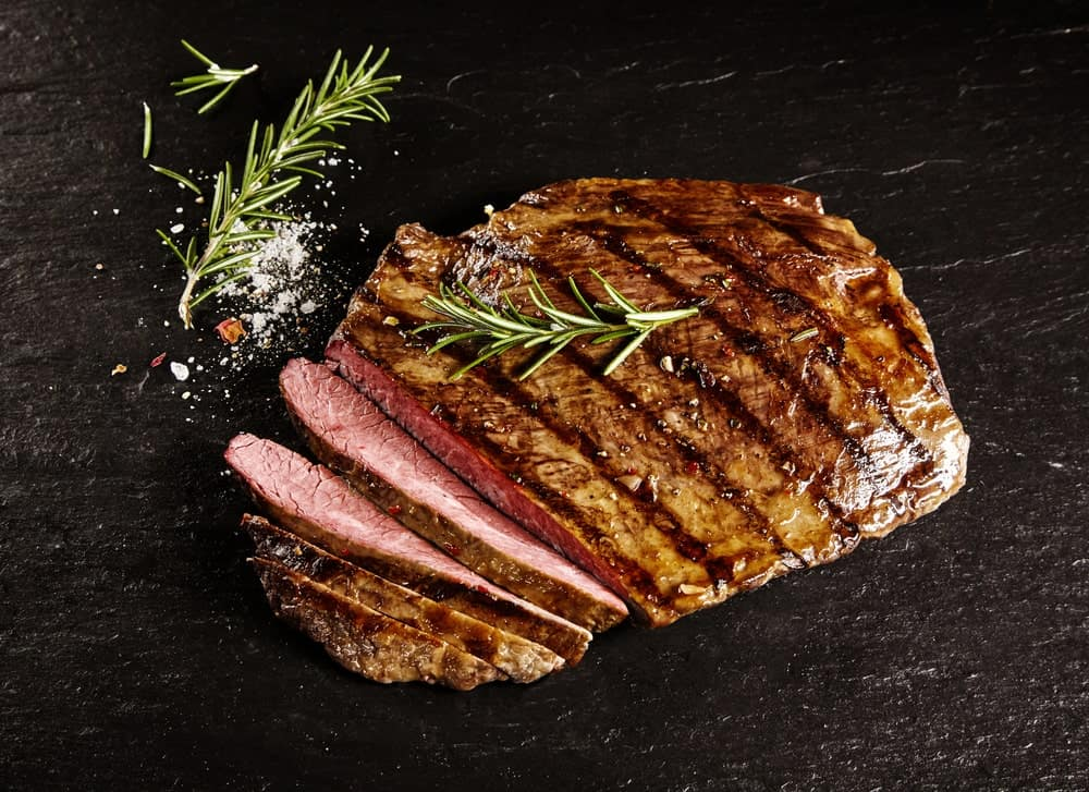 A piece of sliced flank steak with sprigs of rosemary.