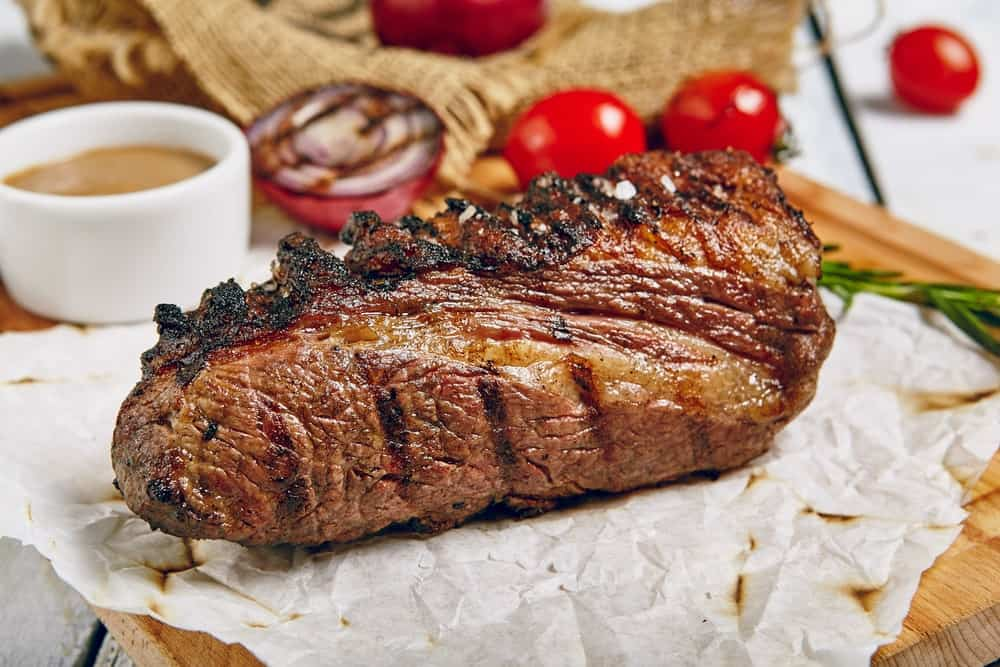 A piece of grilled tri-tip steak with a side of tomatoes.