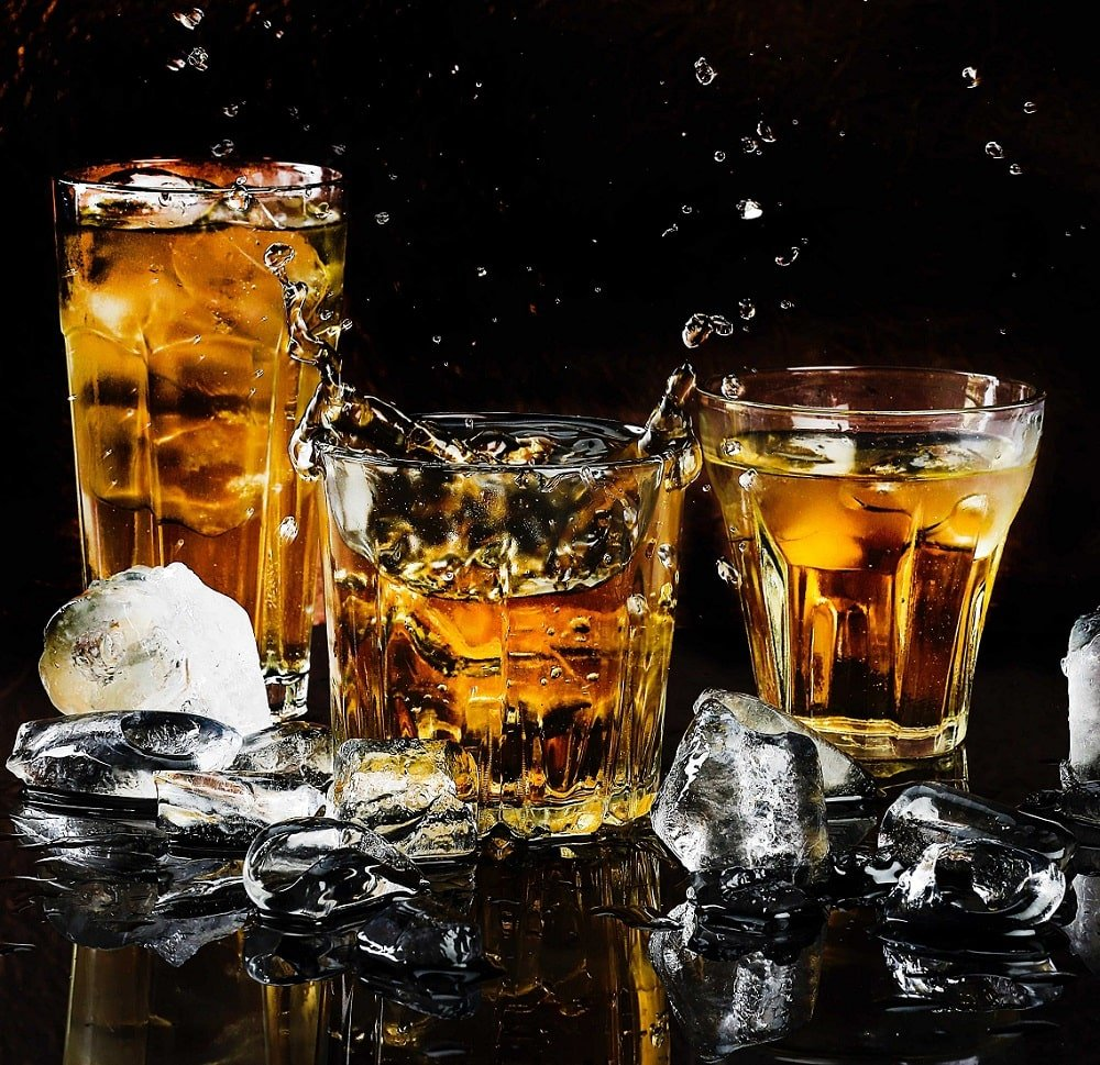 Three glasses of whiskey with ice.