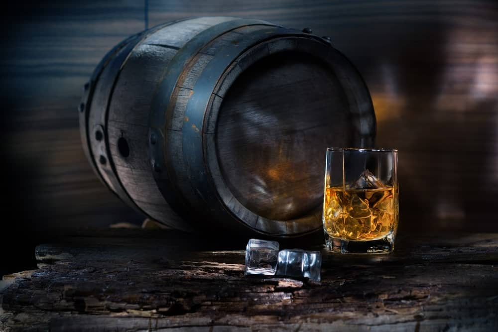 A glass of whiskey with ice next to a barrel of whiskey.