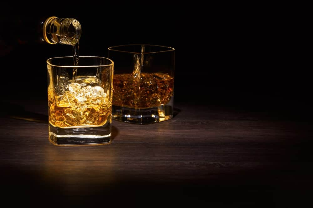 Malt whiskey being poured into a glass with ice.