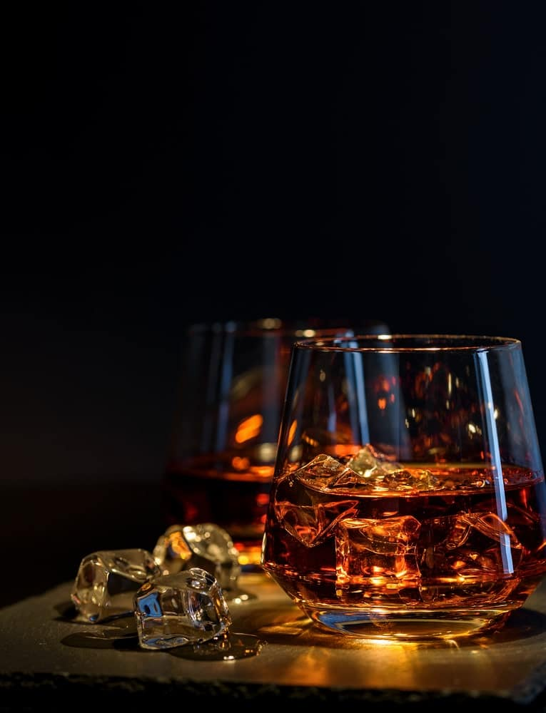 A close look at blended whiskey in a glass with ice.