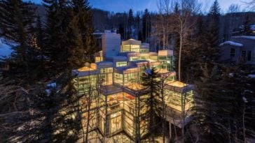 An aerial view of the house featuring the glass walls the make the house glow warm from the interior lights. Image courtesy of Toptenrealestatedeals.com.
