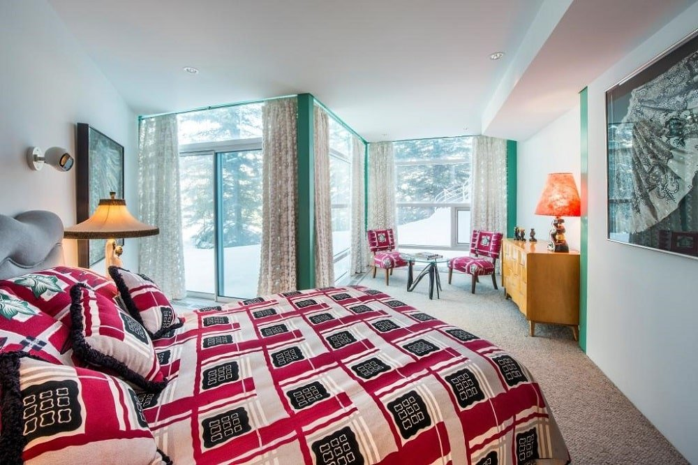 This other bedroom also has a brightly colored and patterned bed that stands out against the bright ceiling and flooring illuminated by the natural lights of the glass walls. Image courtesy of Toptenrealestatedeals.com.
