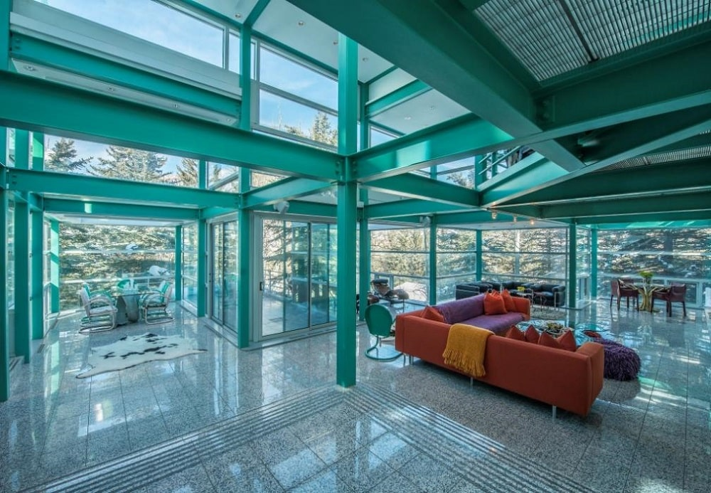 This is the great room of the house with an open design linking the dining area and living room areas complemented by the glass walls. Image courtesy of Toptenrealestatedeals.com.