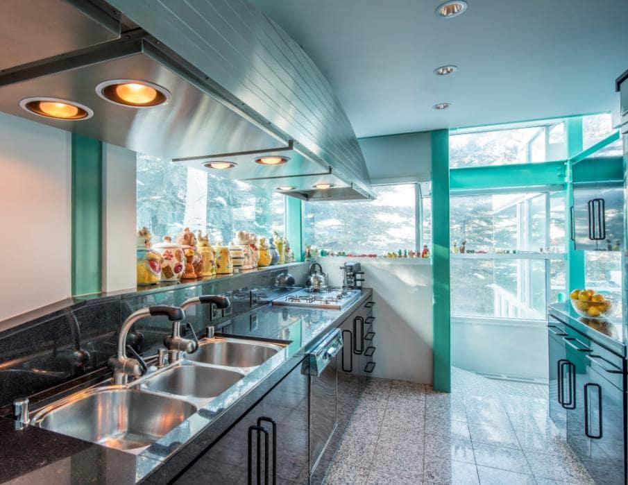 This is a close look at the kitchen with stainless steel hues on its sink and cooking area to match the modern vent hood above. Image courtesy of Toptenrealestatedeals.com.