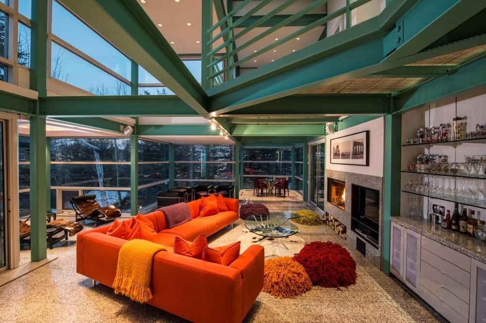 The living room has large metal beams on its ceiling and has glass walls on all sides except the fireplace across from the sofa. Image courtesy of Toptenrealestatedeals.com.