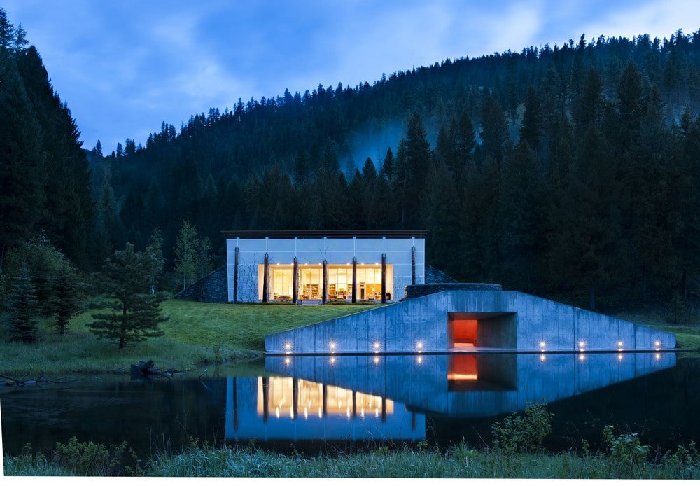 This is a look at the modern main house from the other side of the lake. Here you can see the warm glow of the interiors escaping through the large glass walls. This makes the house stand out against the surrounding landscape of forests and dark mountains. Image courtesy of Toptenrealestatedeals.com.