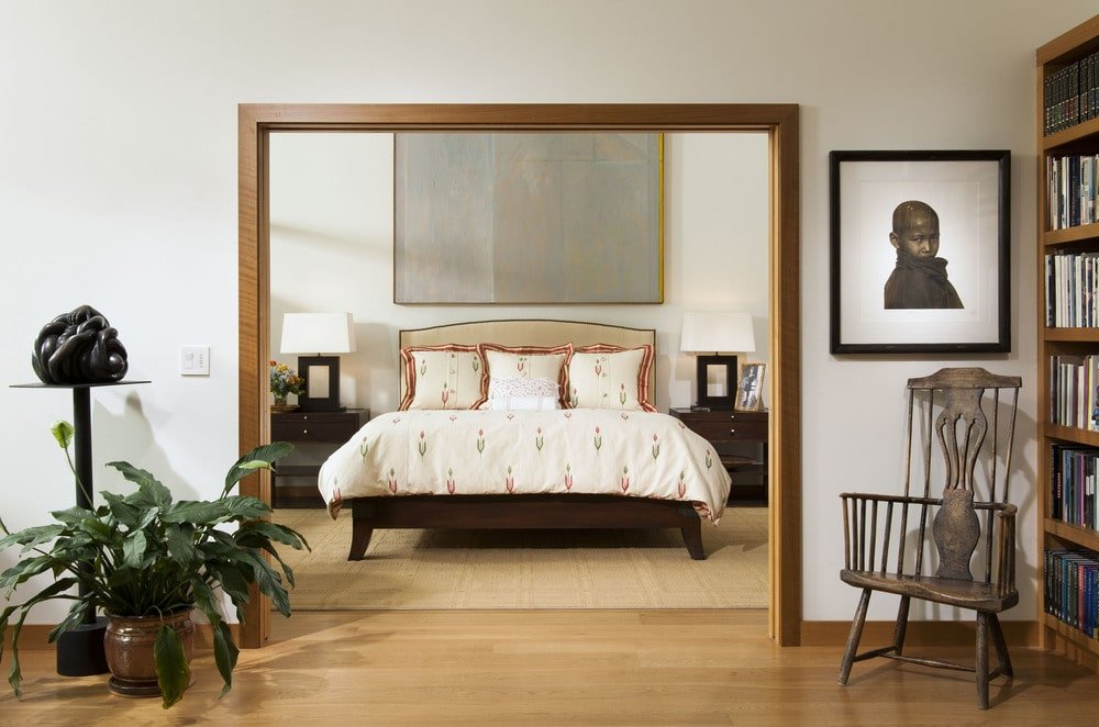 This is a closer look at the large entryway that leads to the bedroom. Here you can see the large bed with a cushioned headboard flanked by bedside drawers and table lamps. Image courtesy of Toptenrealestatedeals.com.