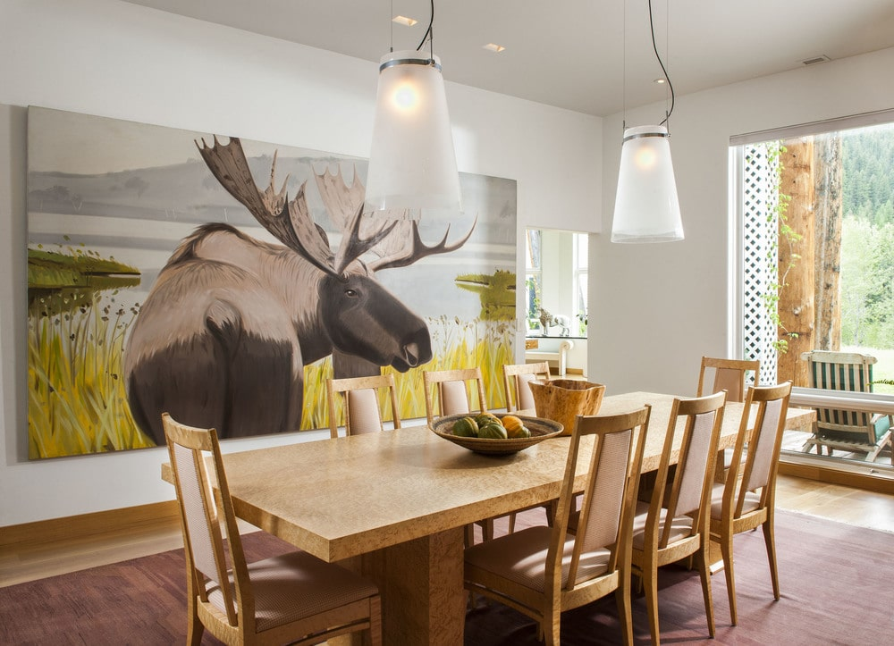 The dining room has a large wooden dining table surrounded by wooden chairs and adorned with a large painting of a moose on the side. Image courtesy of Toptenrealestatedeals.com.