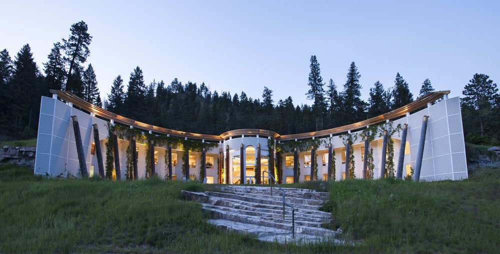 This is the front view of the main house with a curved design and lots of glass walls that glow warmly from the interior lights. Image courtesy of Toptenrealestatedeals.com.