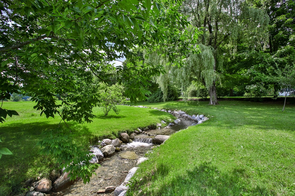 A few yards from the back of the house is a small stream lined with decorative rocks and grass lawns. Image courtesy of Toptenrealestatedeals.com.