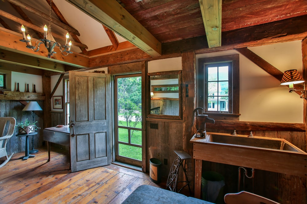 This is the rustic interiors of the wooden cabin that has a beamed ceiling and hardwood flooring. Image courtesy of Toptenrealestatedeals.com.