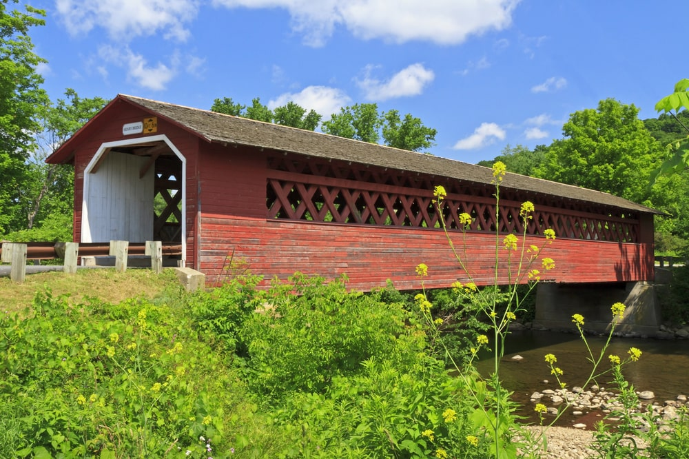 The property also has a wooden covered bridge with a reddish tone to its exterior walls adorned with the surrounding green landscape. Image courtesy of Toptenrealestatedeals.com.