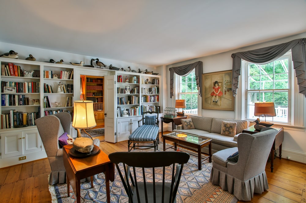 This is the den of the main house with various sofas and chairs complemented by the patterned area rug, wall-mounted artworks and built-in shelves. Image courtesy of Toptenrealestatedeals.com.
