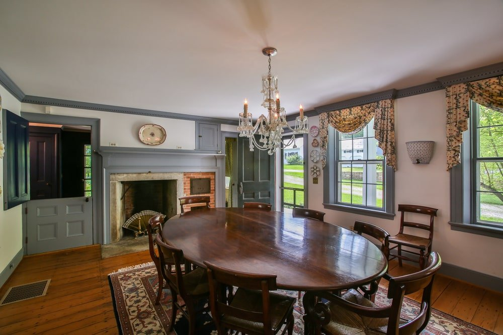 This other view of the dining room shows that there is a large fireplace on the far wall with a gray mantle that matches the window frames. Image courtesy of Toptenrealestatedeals.com.