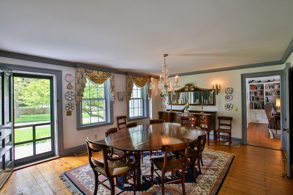 This is the formal dining room of the main house with a large dark wooden dining table surrounded by matching wooden chairs topped with a small chandelier. Image courtesy of Toptenrealestatedeals.com.