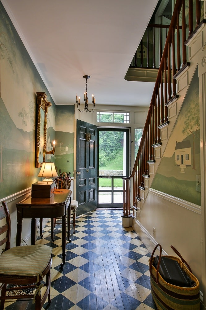 Upon entry of the main house, you are welcomed by this foyer with black and white checkered flooring adorned by clorful murals on the walls along with a console table. Image courtesy of Toptenrealestatedeals.com.
