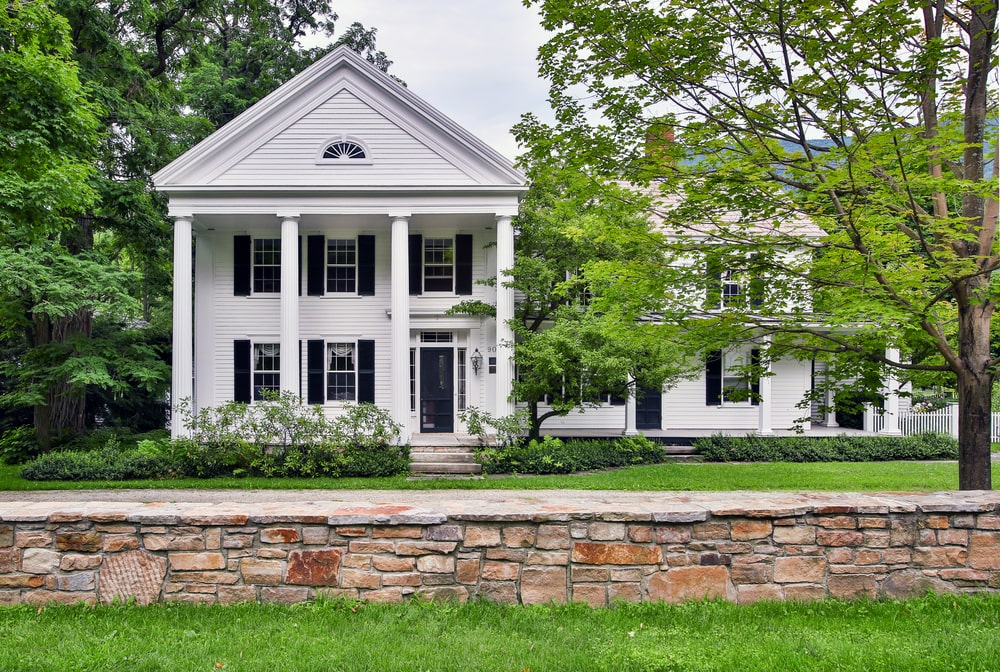 This is the front view of the main house with tall pillars, large windows and a line of shrubs on the side. Image courtesy of Toptenrealestatedeals.com.