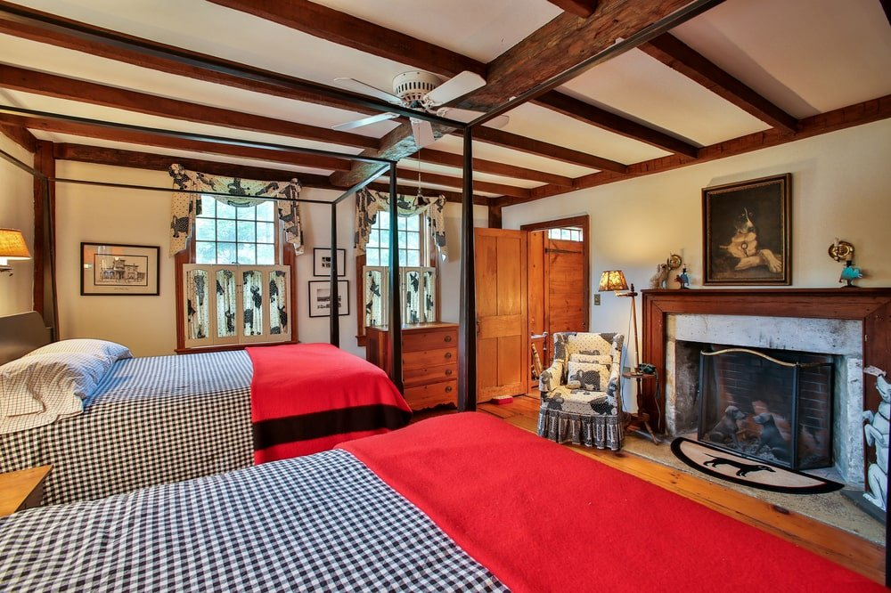 This is the bedroom of the guest house with a couple of wrought-iron four-poster beds across from the fireplace with a wooden mantle. Image courtesy of Toptenrealestatedeals.com.