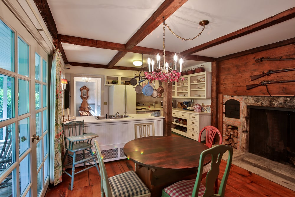 This is the eat-in kitchen of the guest house with beige cabinetry and a round wooden dining table that matches the exposed beams of the ceiling and hardwood flooring. Image courtesy of Toptenrealestatedeals.com.