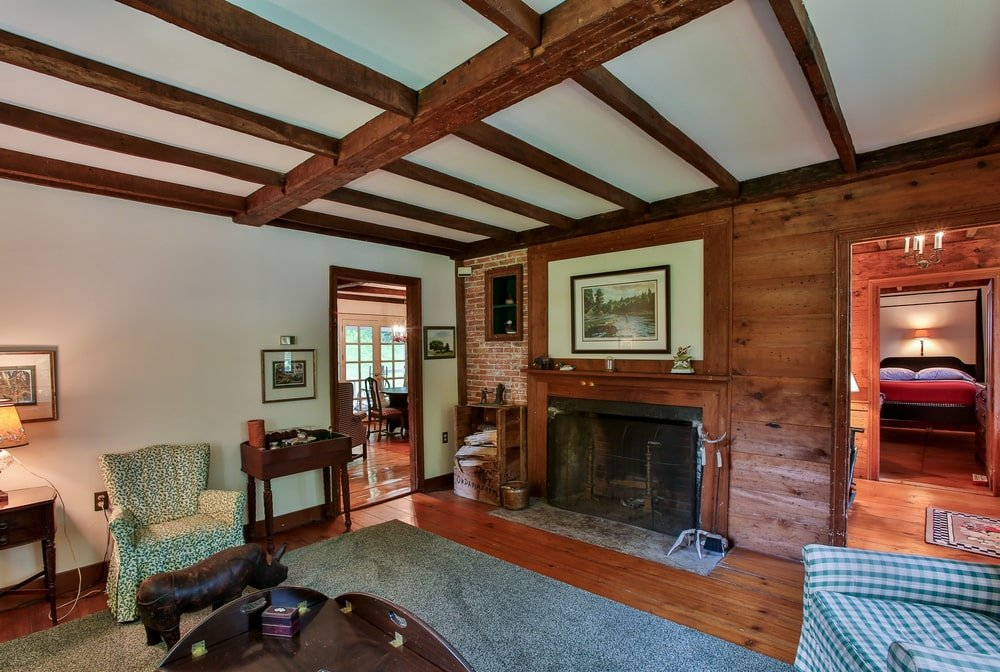 This is the living room of the guest house with a large fireplace that has a wooden mantle that blends with the walls and the exposed beams of the ceiling. Image courtesy of Toptenrealestatedeals.com.